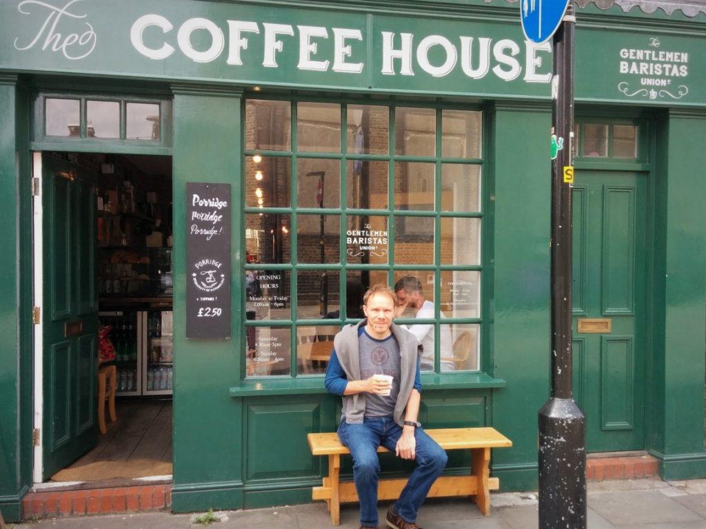 Neil sitting outside a Coffee shop